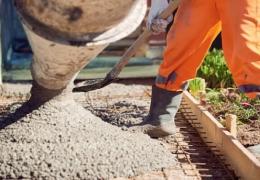 Worker spreading concrete patio