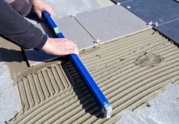 Worker using level on outdoor tiles