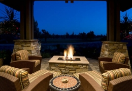 Lit fire pit surrounded by patio furniture at night