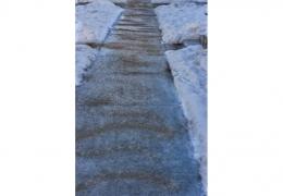 Winter sidewalk covered in rock salt