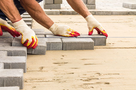 Workers laying paving tiles during construction
